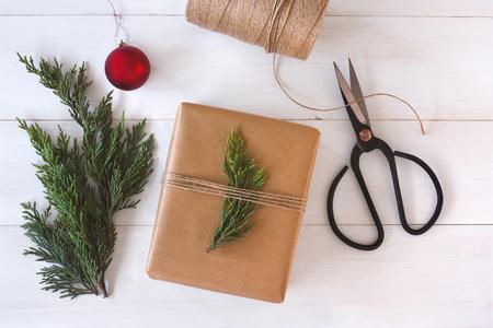 gift tie: Mano mano del regalo en el fondo de madera blanca con decoraci�n de Navidad. Foto de archivo