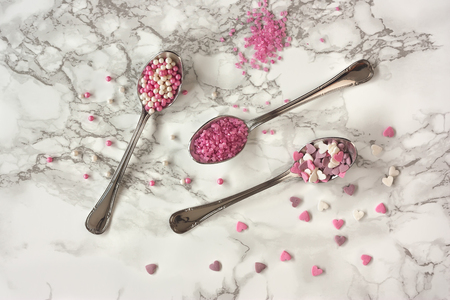 jimmies: Spoons with cupcake sprinkles on marble background Stock Photo