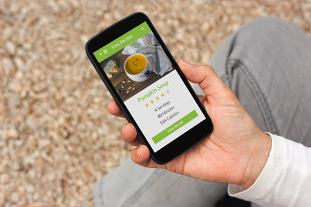 close up food: Hand holding smartphone with food app mock up on screen. All screen content is designed by me Stock Photo