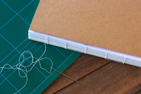 Handbound book with needle and thread on wooden background