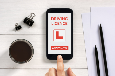 licence: Driving licence app mock up on smart phone screen with office objects on white wooden table. All screen content is designed by me. Stock Photo