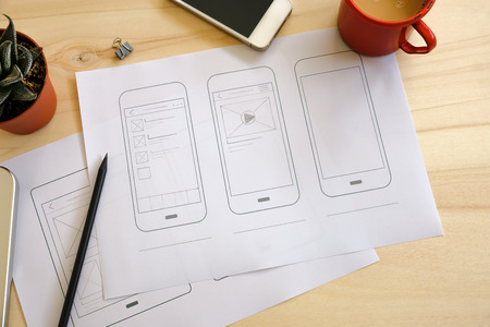 Designer desk with UI wireframe sketches. View from above Standard-Bild