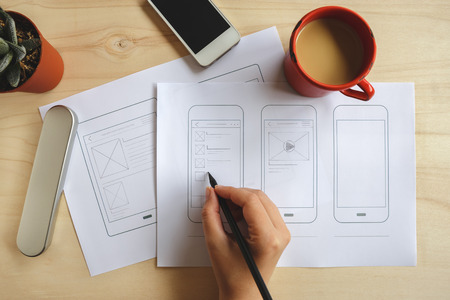 Designer drawing mobile application wireframe on wooden desk. Top view Stock Photo