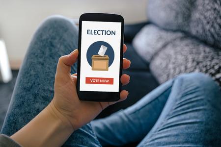 Muchacha que sostiene teléfono inteligente con el concepto de votación en línea en la pantalla. Todo el contenido de la pantalla está diseñado por mí