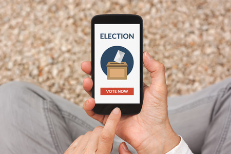 voting: Hands holding smart phone with online voting concept on screen. All screen content is designed by me. Flat lay Stock Photo
