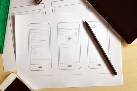 prototype: Designer desk with paper prototype of a mobile application. Flat lay.
