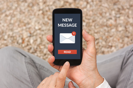 incoming: Hands holding smart phone with new message concept on screen. All screen content is designed by me Stock Photo