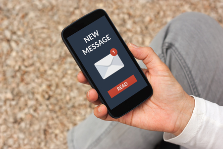 Hand holding smart phone with new message concept on screen. All screen content is designed by me Stock Photo