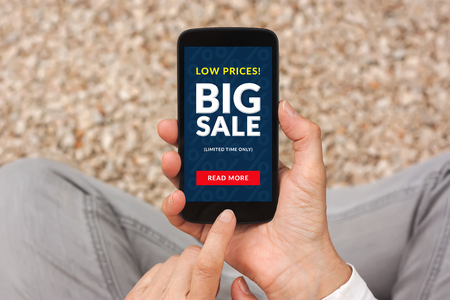 cheapness: Hands holding smart phone with big sale concept on screen. All screen content is designed by me