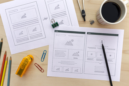 Designer desk with website wireframe sketches. Flat lay