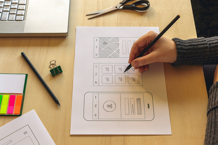 デザイナー wireframing 木製机の上の携帯アプリ 写真素材