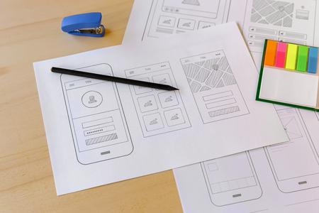 prototypes: Mobile app prototypes on designer wooden desk.