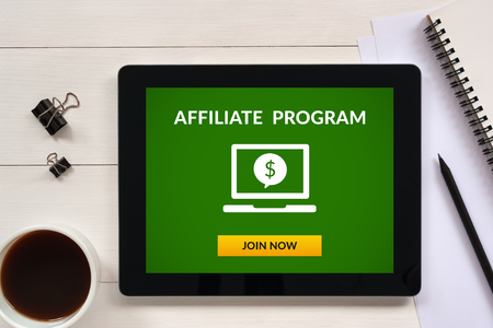 Affiliate program concept on tablet screen with office objects on white wooden table. All screen content is designed by me. Flat lay Stock Photo