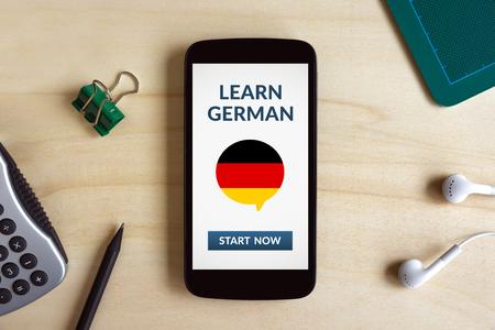 Leer Duits concept op het slimme telefoonscherm op houten bureau. Alle scherminhoud is door mij ontworpen. Plat leggen