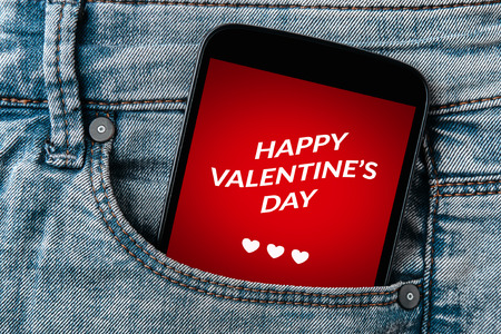 Valentine's day concept on smartphone screen in jeans pocket. All screen content is designed by me. Flat lay