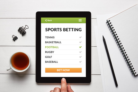 Sports betting concept on tablet screen with office objects on white wooden table. All screen content is designed by me. Flat lay Stock Photo