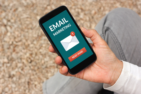 Hand holding smart phone with email marketing concept on screen. All screen content is designed by me