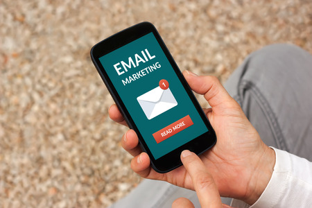 Hands holding smart phone with email marketing concept on screen. All screen content is designed by me
