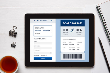 Boarding pass concept on tablet screen with office objects on white wooden table. All screen content is designed by me. Flat lay