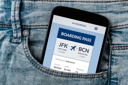 Boarding pass concept on smartphone screen in jeans pocket. All screen content is designed by me. Flat lay