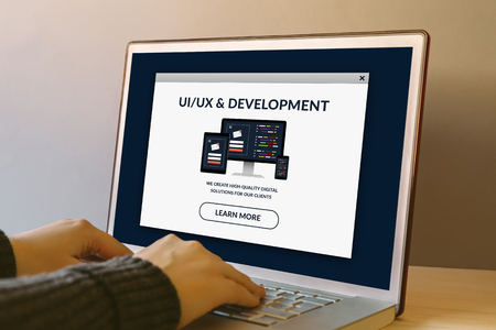 UI/UX design and development concept on laptop computer screen on wooden table. Hands typing on a keyboard. All screen content is designed by me.