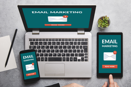Email marketing concept on laptop, tablet and smartphone screen over gray table. All screen content is designed by me. Flat lay Stock Photo