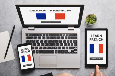 Learn French concept on laptop, tablet and smartphone screen over gray table. All screen content is designed by me. Flat lay 免版税图像