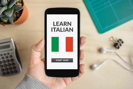 Hand holding smart phone with learn Italian concept on screen. Top view Banco de Imagens