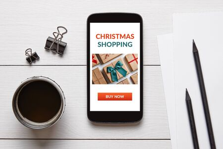 Christmas shopping concept on smart phone screen with office objects on white wooden table. Top view 스톡 콘텐츠