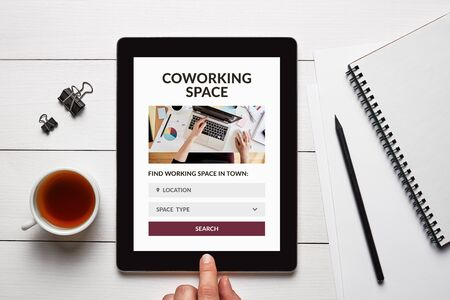 Coworking space concept on tablet screen with office objects on white wooden table. Top view Stok Fotoğraf