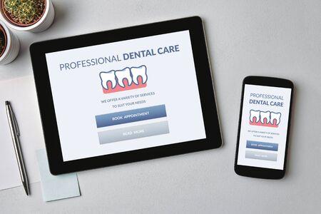 Concept de soins dentaires sur tablette et écran de smartphone sur table grise. Vue de dessus