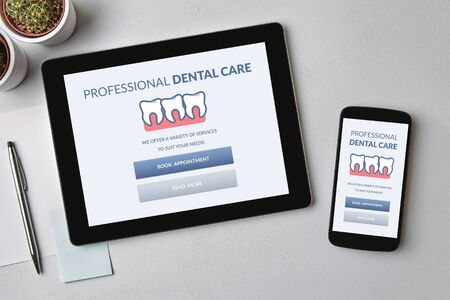 Dental care concept on tablet and smartphone screen over gray table. Top view