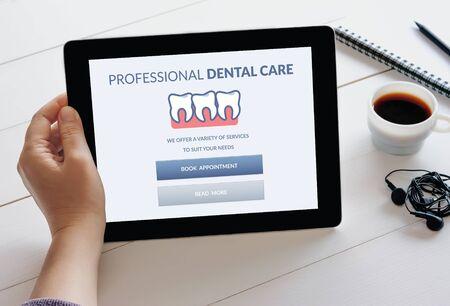 Mano que sostiene la tableta digital con concepto de atención dental en la pantalla.