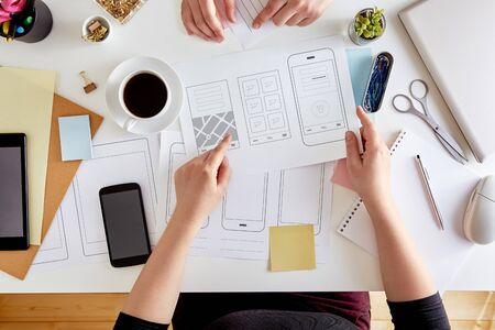 UX graphic designers planning out the structure of a mobile application. Wireframing stage of a web mobile phone. User experience concept. Flat lay