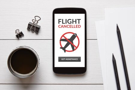 Flight cancelled concept on smart phone screen with office objects on white wooden table. Top view Foto de archivo