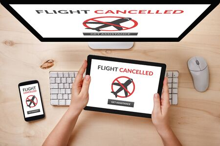 Flight cancelled concept on computer, tablet and smartphone screen over wooden table. Top view of responsive devices.