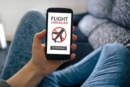 Girl holding smart phone with flight cancelled concept on screen Standard-Bild