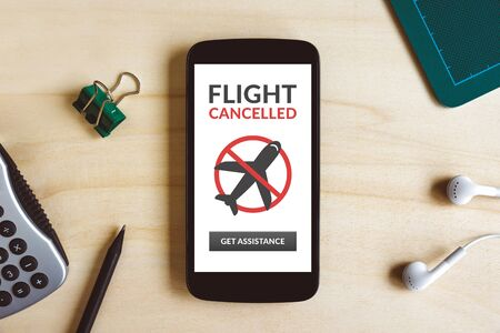 Flight cancelled concept on smart phone screen on wooden desk. Top view