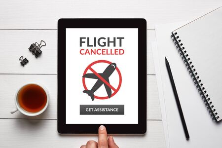 Flight cancelled concept on tablet screen with office objects on white wooden table. Top view