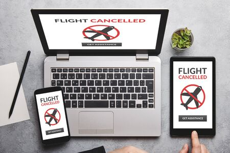 Flight cancelled concept on laptop, tablet and smartphone screen over gray table. Flat lay