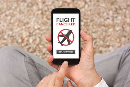 Hands holding smart phone with flight cancelled concept on screen. Top view Standard-Bild