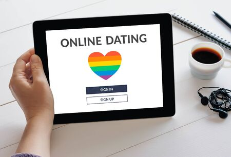 Hand holding digital tablet computer with dating app concept on screen.  online dating. Standard-Bild