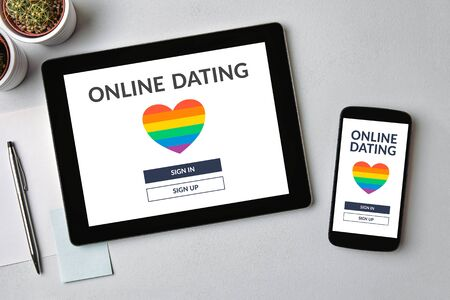 Dating app concept on tablet and mobile phone screen over gray table. Online dating. Top view