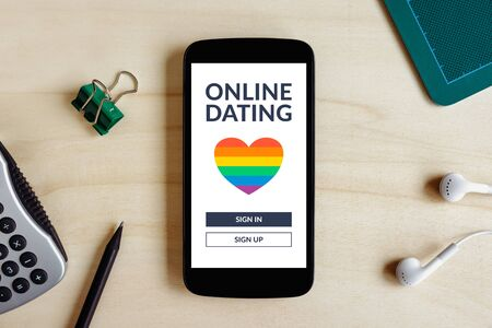 LGBT dating app concept on smart phone screen on wooden desk. Gay online dating. Top view Standard-Bild