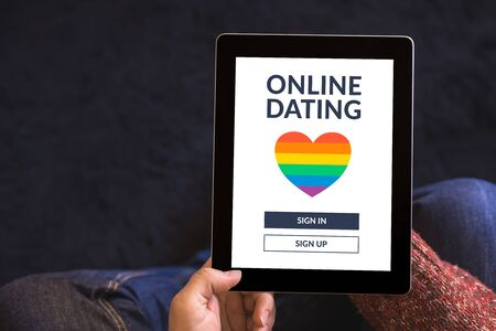 Hands holding digital tablet computer with LGBT dating app concept on screen. Gay online dating. Copy space. Top view
