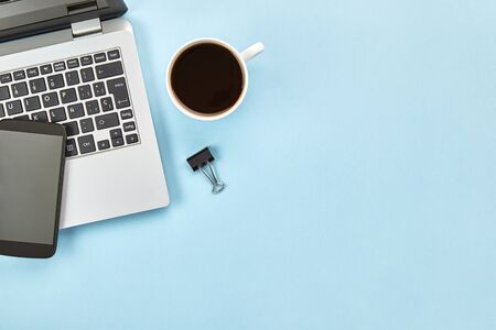 Flat lay image of blue workspace with laptop, smartphone, coffee and copy space. Hero header concept. Top view.