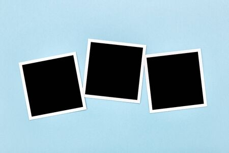 Blank empty vintage photo frames templates on blue background. Instant photos mockup. Flat lay