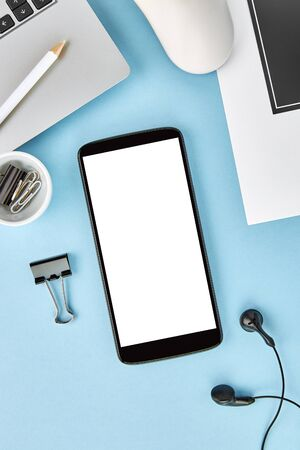 Vertical mockup image of a smartphone with blank white screen on blue surface. Flat lay