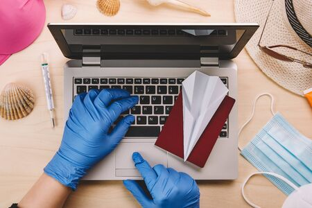 Coronavirus and travel concept. Woman with blue latex gloves using a laptop to book summer holidays during the coronavirus pandemic. Flat lay