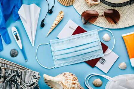 Overhead view of coronavirus travel accessories on blue background. Essential summer vacation items during the coronavirus pandemic. Covid-19 and travel concept.